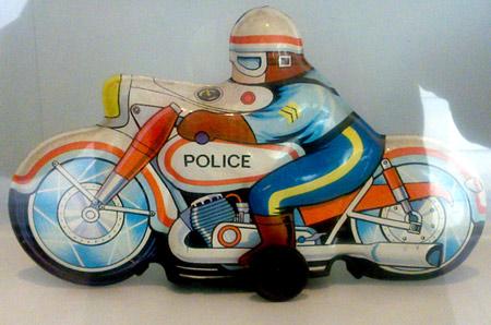 foto de una moto de juguete antigua, con colores primarios, naranja, azul, amarillo y marrón