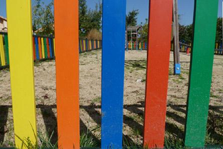 foto de la valla de un parque infantil, con colores primarios, amarillo,naranja,azul,rojo y verde